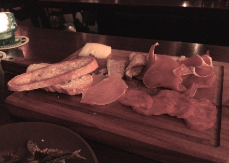 Charcuterie platter with a selection of meats, local chutney, toasted bread and manchego cheese.