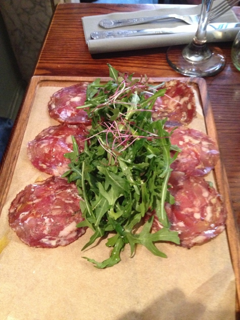 Wild boar and venison salami with a rocket salad and extra virgin olive oil.