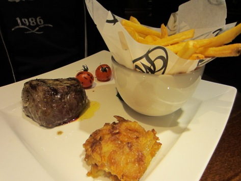 Fillet steak with fries, cherry tomatoes and onion loaf.