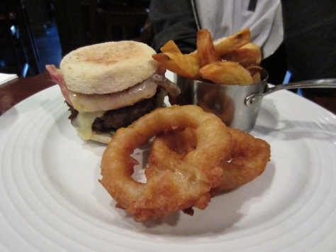 Homemade burger with cheese, crispy bacon, crispy onion rings and dripping cooked chips.