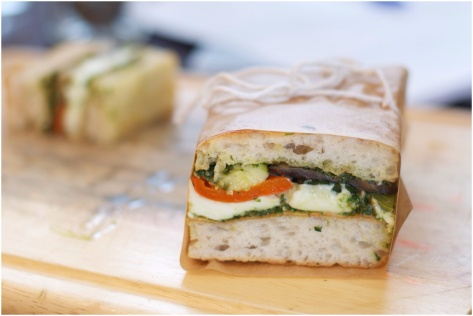 Pressed foccacia sandwich with buffalo mozzarella, roasted vegetables and basil pesto